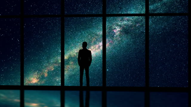 the male standing near the window on the starry sky background. time lapse - бесконечность стоковые видео и кадры b-roll