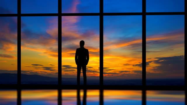 vidéos et rushes de le homme debout près de fenêtre sur un fond de coucher de soleil. time-lapse - raclette