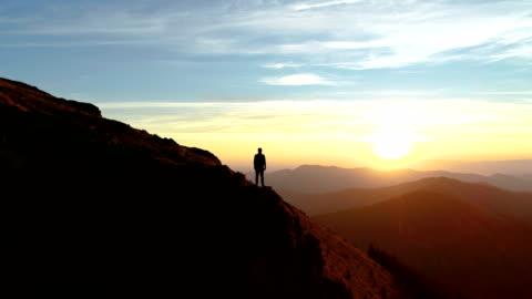 das männchen steht auf dem berg und genießt den malerischen sonnenuntergang - alpen stock-videos und b-roll-filmmaterial