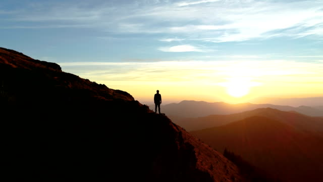the male standing on the mountain and enjoying the picturesque sunset - европейские альпы стоковые видео и кадры b-roll