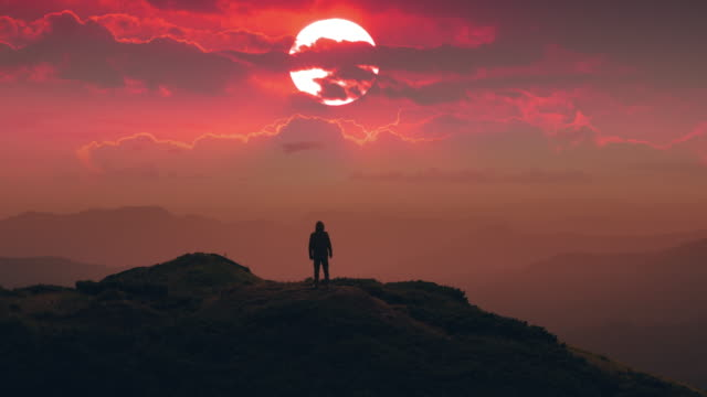 The male standing on the mountain top against the picturesque sunset. time lapse The male standing on the mountain top against the picturesque sunset. time lapse mountains in mist stock videos & royalty-free footage
