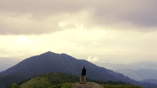 the male standing on the mountain with a picturesque view - stare in piedi video stock e b–roll
