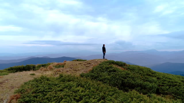 The male standing on the mountain with a scenic landscape. time lapse