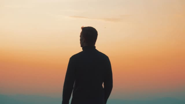 The male standing on the rock against the sunset background