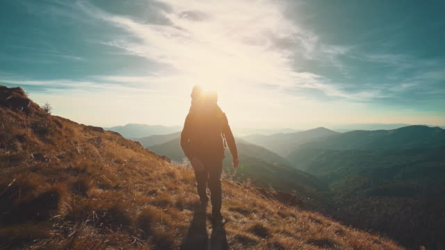 The male walking along the mountain on the bright sunset background. slow motion
