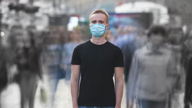 the male with medical face mask stands in the middle of urban space. time lapse - mask стоковые видео и кадры b-roll