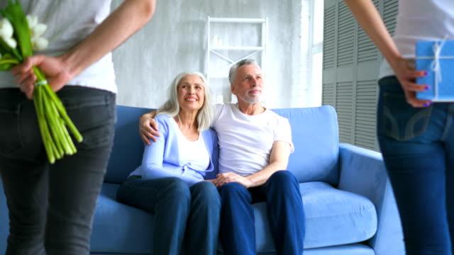 L'homme et une femme donner un cadeau avec des fleurs à un vieux couple - Vidéo