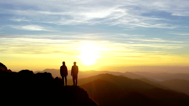 The man and a woman on the mountain watching to the beautiful landscape