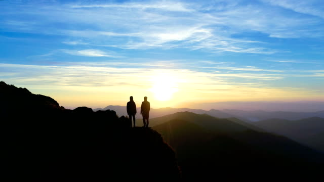 The man and a woman on the mountain watching to the picturesque landscape