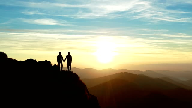 The man and a woman standing on the mountain and watching to a beautiful sunrise
