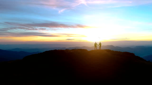 The man and a woman standing on the mountain on the sunrise background