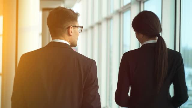 vídeos de stock e filmes b-roll de the man and a woman walking near windows in the office center. slow motion - envolvimento dos funcionários