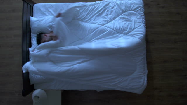 mannen och kvinnan har sex under täckmantel i sängen. nattetid. vy uppifrån - duntäcke bildbanksvideor och videomaterial från bakom kulisserna