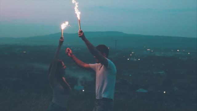 The man and woman have fun with sparklers burning sticks outdoor. slow motion