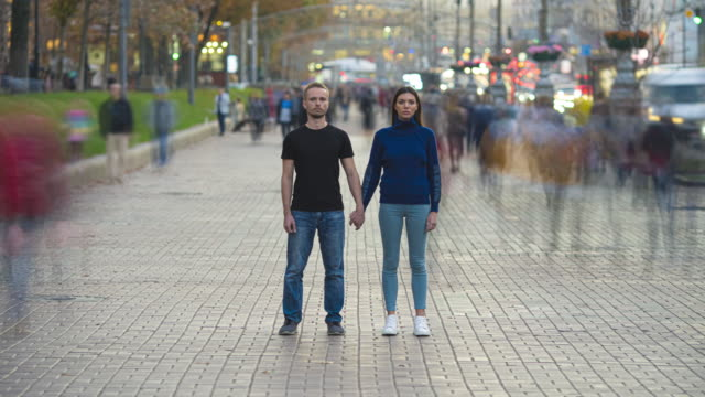 Video The man and woman hold hands and stand in the crowdy flow. time lapse