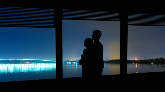 the man and woman hug near the window on a city river background. time lapse - man look sky scraper video stock e b–roll
