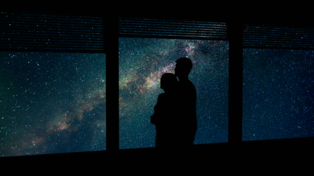 the man and woman hug near the window on a meteor shower background. time lapse - man look sky scraper video stock e b–roll