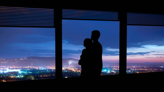 the man and woman hug near the window on a night city background. time lapse - man look sky scraper video stock e b–roll