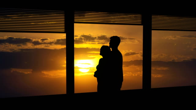 the man and woman hug near the window on a sun background. time lapse - man look sky scraper video stock e b–roll