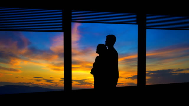 the man and woman hug near the window on a sunset background. time lapse - man look sky scraper video stock e b–roll
