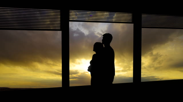 the man and woman hug near the window on sunset background. time lapse - man look sky scraper video stock e b–roll