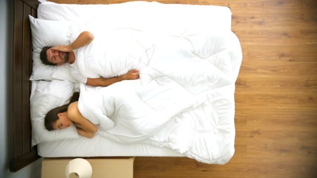 the man and woman sleeping in the bed. view from above - sezione superiore video stock e b–roll