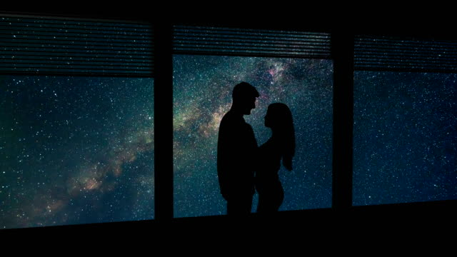 the man and woman stand near a window on the starry sky background. time lapse - man look sky scraper video stock e b–roll