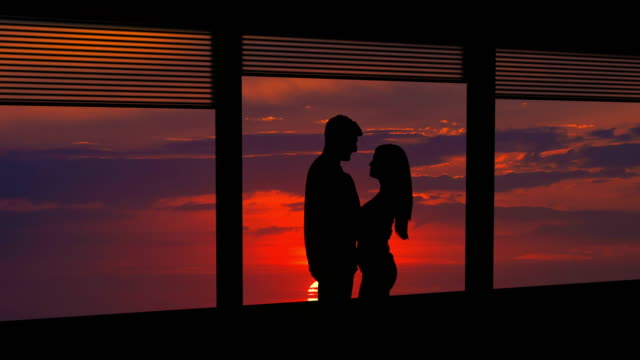 the man and woman stand near the window on a bright sun background. time lapse - man look sky scraper video stock e b–roll