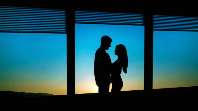 the man and woman stand near the window on a starry sky background. time lapse - man look sky scraper video stock e b–roll