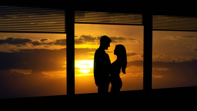 the man and woman stand near the window on a sunset background. time lapse - man look sky scraper video stock e b–roll