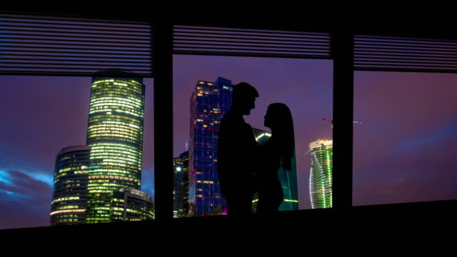 the man and woman stand near the window on skyscrapers background. time lapse - man look sky scraper video stock e b–roll