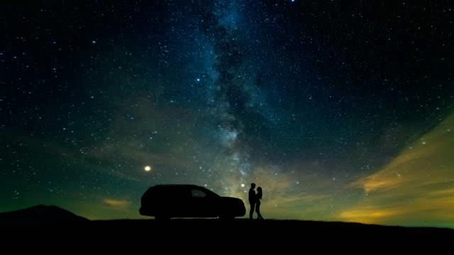 星空に対して車の近くに立っている男と女。時間経過 - 星型点の映像素材/bロール