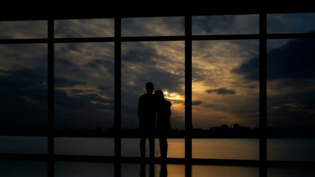 the man and woman standing near windows on a sundown background. time lapse - man look sky scraper video stock e b–roll