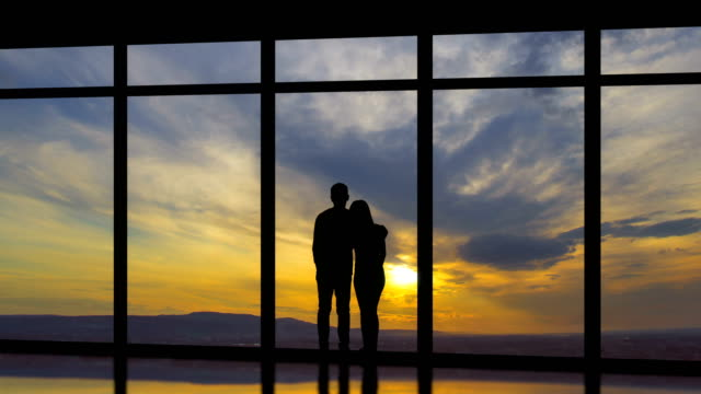 the man and woman standing near windows on a sunset background. time lapse - man look sky scraper video stock e b–roll