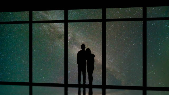 the man and woman standing near windows on the starry sky background. time lapse - man look sky scraper video stock e b–roll