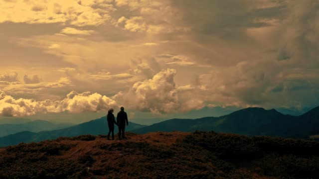 The man and woman standing on a beautiful mountain