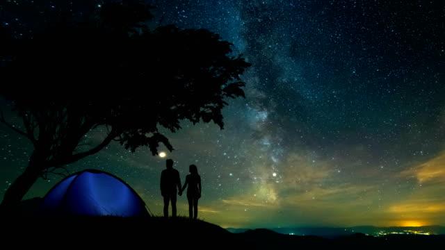 木の近くの山の上に立っている男と女。時間経過 - 星型点の映像素材/bロール