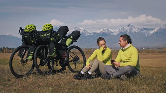男女は自転車梱包でツーリング混合地形サイクルで旅行します。二人は自転車のバッグを持って旅をします。山の雪が覆われています。 - スポーツ用品点の映像素材/bロール