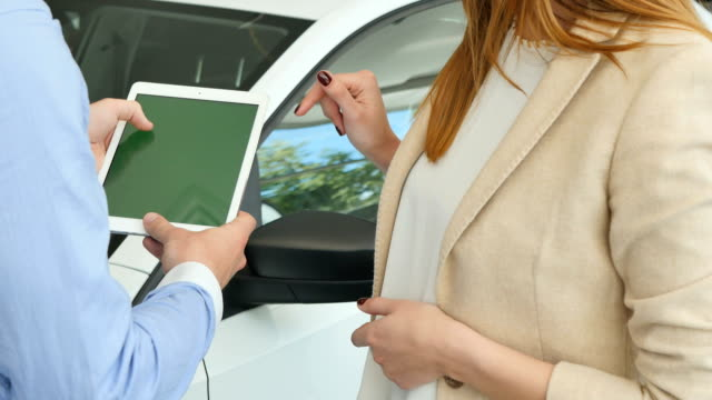 The man and woman using the tablet in the car showroom video