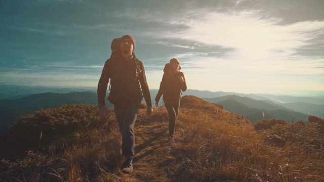 The man and woman walking along the mountain on a sunny background. slow motion The man and woman walking along the mountain on a sunny background. slow motion hiking stock videos & royalty-free footage