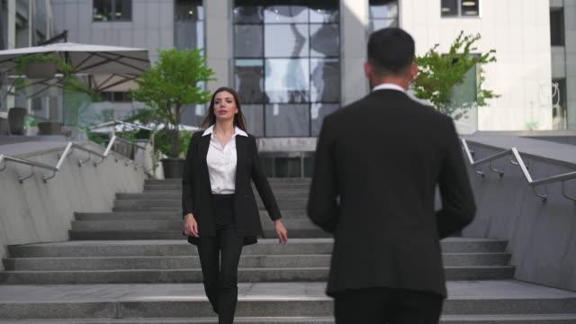 stockvideo's en b-roll-footage met de man en vrouw lopen naar elkaar in de buurt van business center. slow motion - flirten