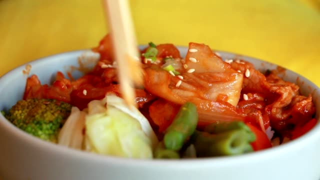 The man ate the traditional Korean cabbage kimchi and pork from a ceramic bowl with chopsticks. video