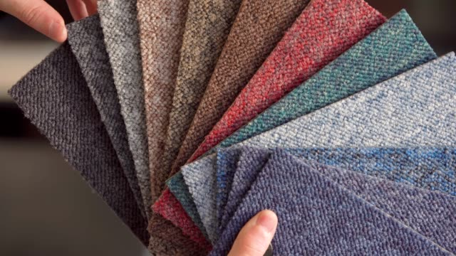 the man chooses the color of the new carpet according to the pattern book in the flooring shop.