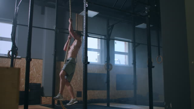 the man climbs up the rope and reaches the top. the concept of success through hard work - inerpicarsi video stock e b–roll