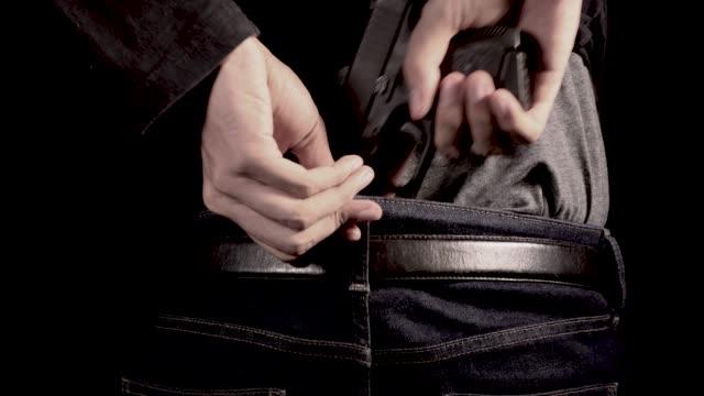 mannen dölja pistol bakom hans rygg - byxor bildbanksvideor och videomaterial från bakom kulisserna