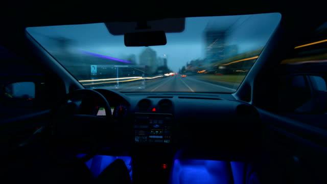 mannen som körde en bil med en virtuell navigator i kvälls staden. hyperlapse - vindruta bildbanksvideor och videomaterial från bakom kulisserna