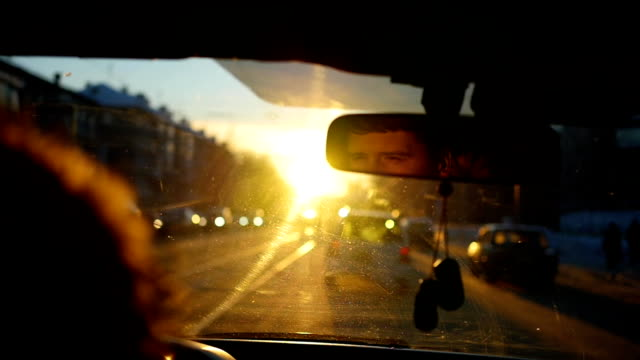 The man driving the car under sunset sky reflection in the rear view mirror The man driving the car under sunset sky. Face reflection in the rear view mirror rear view mirror stock videos & royalty-free footage