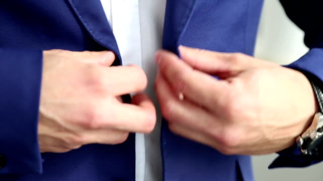 The man fasten the button on his jacket