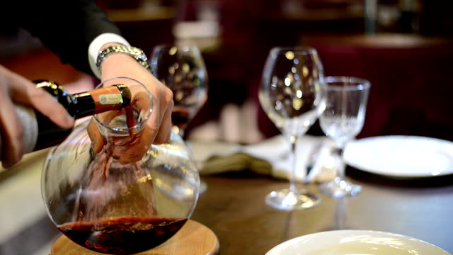 the man hand pouring the red wine from bottle  into the decanter - decanter video stock e b–roll