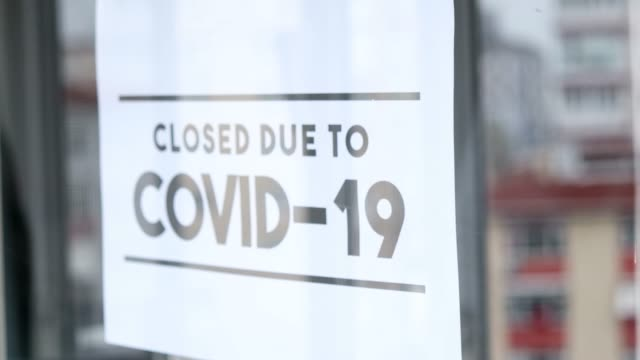 "the man hanging the sign ""closed due to covid-19"" on the glass of the shop because of the coronavirus. - chiuso video stock e b–roll"